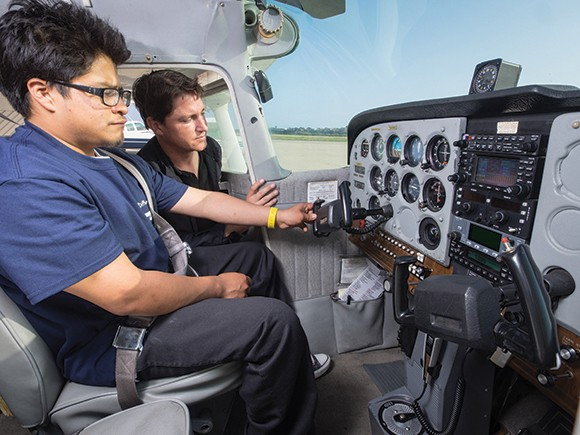Flight instructor Bill Peterson performs a preflight inspection with student Luis Santos as part of the programs held by A Different Point of View, a nonprofit flight school for underprivileged students. The nonprofit will compete in Fast Pitch SB next month. (Nik Blaskovich / Business Times photo)