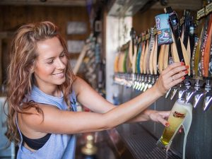 Terra Lee Inglis, bar manager at Figueroa Mountain Brewing Co., pours a draft beer for a customer. (Nik Blaskovich / Business Times photo)