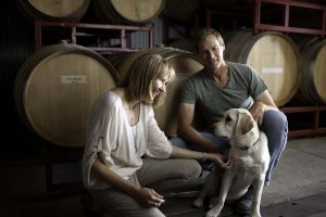 Terry and Jennifer Hoage in their winery's barrel room with their 2-year-old Labrador, Lexi.